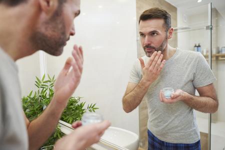 Man applying face cream on his face in bathroom