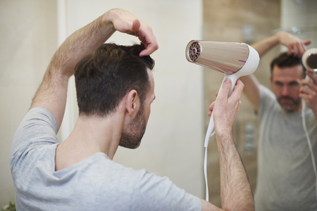 Rear view of man drying his hair in bathroom