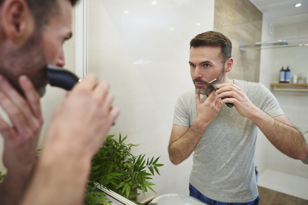 Mature man with electric razor shaving in bathroom