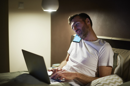 Man talking by mobile phone and using laptop in bed Stock fotó