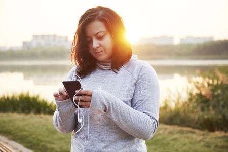 Female athlete using a mobile phone in public park Stock Photo