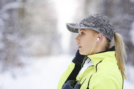 Side view of female athlete listening to music