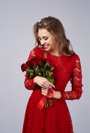 Happy woman holding a bunch of fresh roses