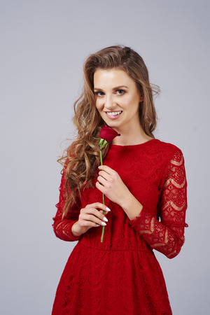 Beautiful woman with red rose in the studio shot Stock Photo