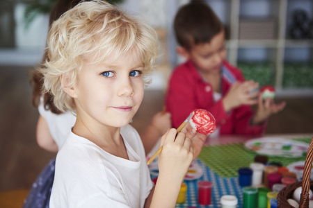 Portrait of smiling boy painting easter eggs