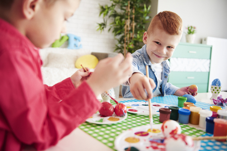 Smiling boy painting easter eggs Stock Photo