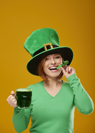 Woman with a party horn blower and a beer glass