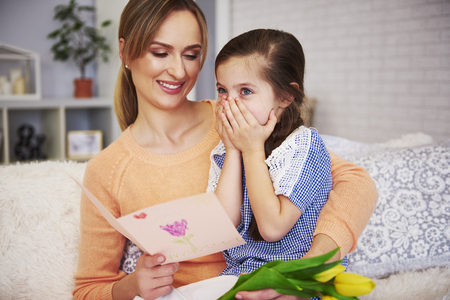 Young mom reading Mothers Day greeting card Imagens