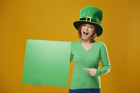 Portrait of screaming leprechaun pointing at banner with copy space Stock Photo