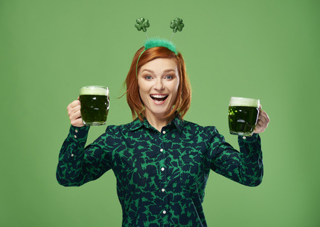 Excited woman with beer making a toast in studio shot
