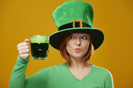 Playful woman with leprechauns hat looking at beer