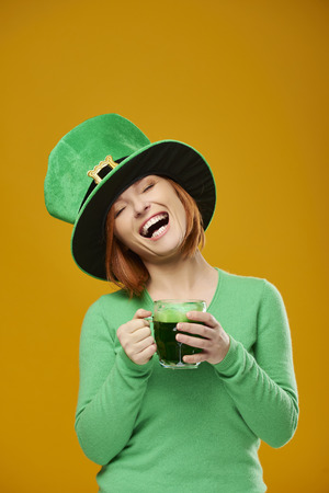 Happy woman with leprechauns hat drinking beer