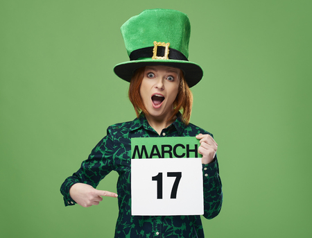 Screaming woman with leprechauns hat pointing at calendar