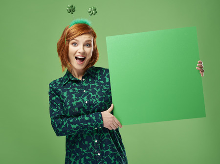 Portrait of screaming woman holding green banner with copy space