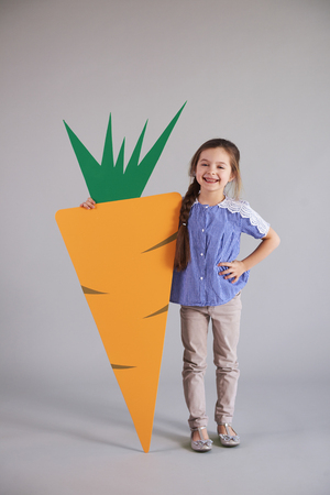 Smiling girl holding a big, artificial carrot in studio shot