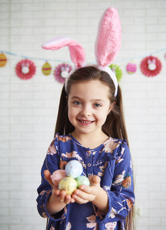 Portrait of girl with bunny ears holding colorful easter eggs