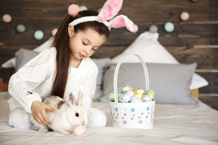 Girl playing with rabbit in bedroom Imagens
