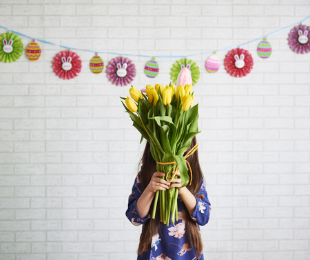 Girl holding bunch of tulips in front of her face Imagens
