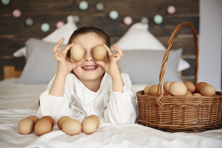 Girl holding eggs in front of her eyes Imagens