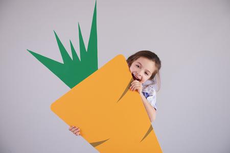 Playful girl eating a big carrot Imagens
