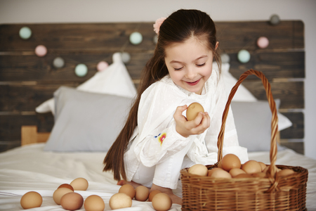 Cheerful girl watching the eggs in bed