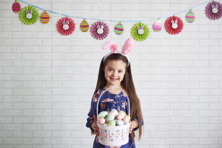 Portrait of smiling child holding a basket of easter eggs
