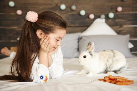 Cheerful girl looking at rabbit Imagens