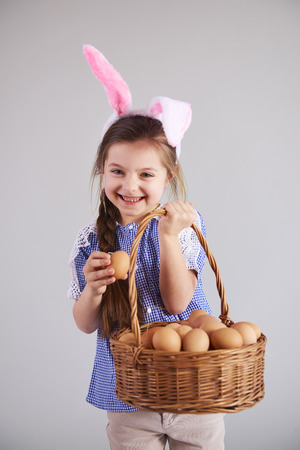 Smiling woman in rabbit costume holding a basket of eggs Imagens