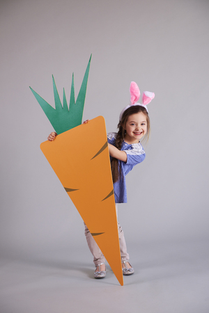 Adorable girl with bunny ears holding a big carrot