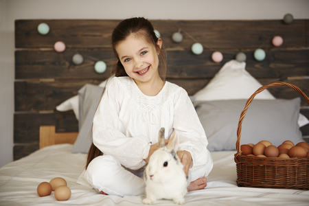 Portrait of girl with rabbit and easter basket of eggs Imagens