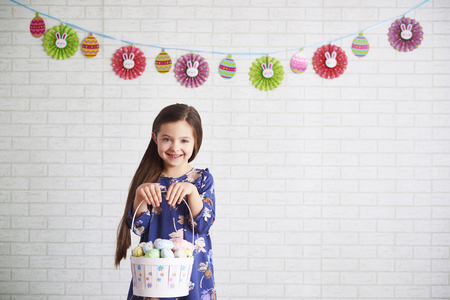 Smiling child holding a basket of easter eggs