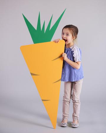 Playful girl eating a huge, artificial carrot