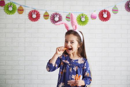Child in rabbit costume eating carrots Imagens