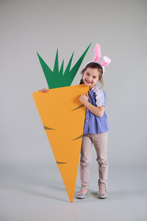 Portrait of child in easter bunny costume holding big carrot