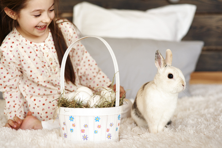 Girl having fun with rabbit in bedroom