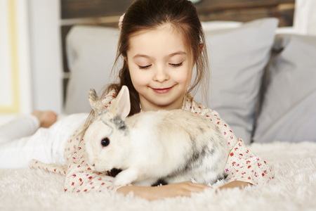 Affectionate girl playing with rabbit Imagens