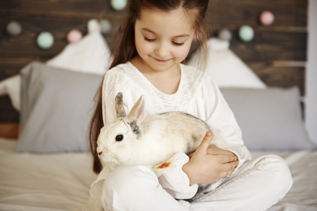 Close up of girl embracing fluffy rabbit Imagens