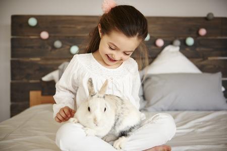 Happy girl and rabbit in bedroom