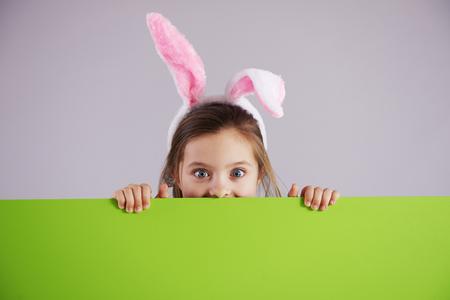 Girl in rabbit costume holding green banner