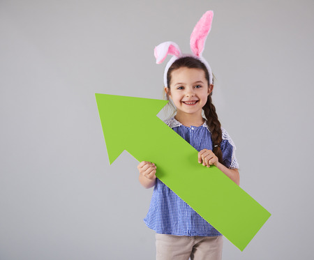 Smiling girl with green arrow pointing at copy space Imagens