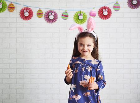 Portrait of cute girl in rabbit costume eating carrots Imagens