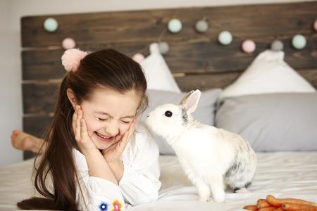 Shot of rabbit kissing happy girl