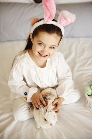 Smiling girl is stroking fluffy rabbit
