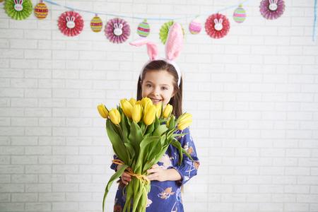 Happy girl holding bunch of yellow tulips