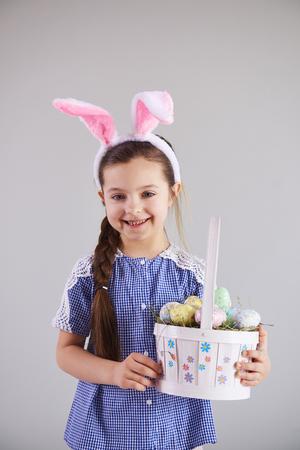 Smiling girl holding a basket of easter eggs