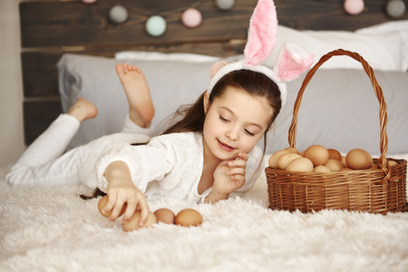 Happy child playing with eggs in bedroom Imagens