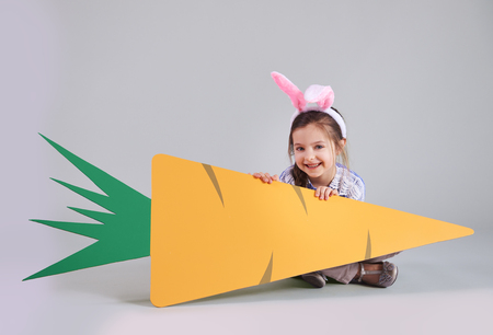 Smiling girl holding a big carrot with copy space