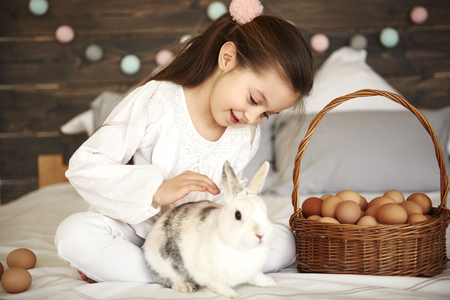 Affectionate girl stroking her rabbit in bed