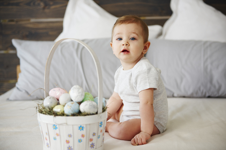 Adorable baby girl with basket of easter eggs Imagens