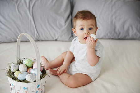 Playful baby eating easter egg on the bed